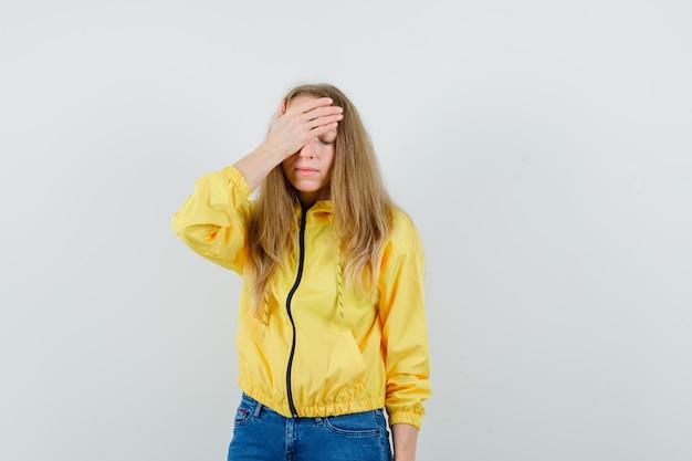 Blonde dame hand op voorhoofd in jas, spijkerbroek en op zoek vergeetachtig,