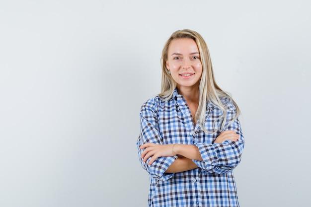 Blonde dame in casual overhemd permanent met gekruiste armen en op zoek blij