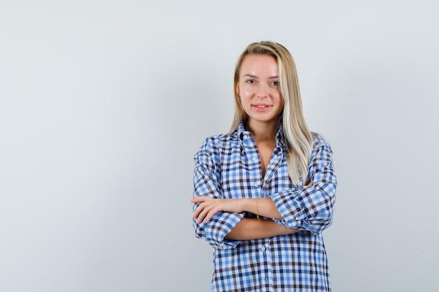 Blonde dame in casual overhemd permanent met gekruiste armen en op zoek zelfverzekerd