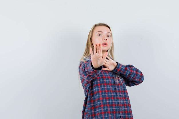 Blonde dame in casual shirt met stop gebaar en op zoek naar strikte, vooraanzicht.