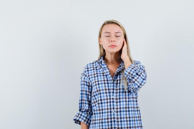 Blonde dame in geruit overhemd die de gezichtshuid op haar wang aanraakt en er ontspannen uitziet