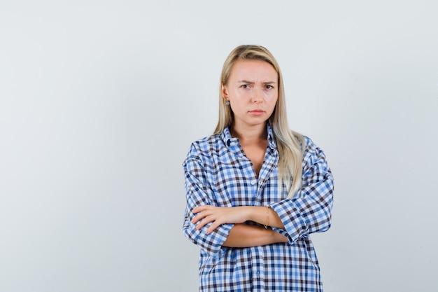 Blonde dame in ingecheckte overhemd permanent met gekruiste armen en boos kijkt