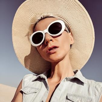 Blonde dame in modeaccessoires. hoed en zonnebril. alleen strandvibes