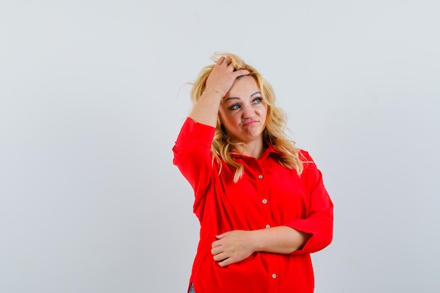 Blonde dame in rood overhemd haar haarruimte voor tekst aan te passen