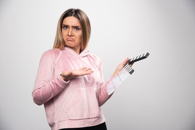 Blonde dame in roze sweatshirt die een leeg klepelbord vasthoudt en probeert te begrijpen wat het is.