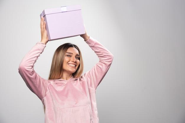 Blonde dame in roze sweatshirt houdt een geschenkdoos boven haar hoofd en schudt.