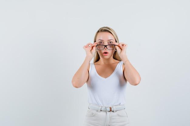 Blonde dame in singlet, broek die bril opstijgt en gefocust kijkt, vooraanzicht.