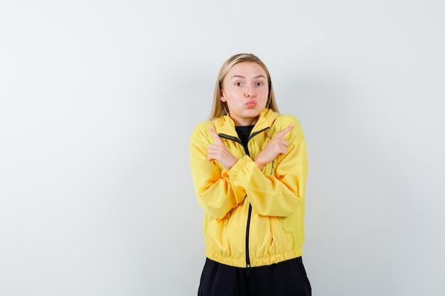 Blonde dame in trainingspak die omhoog wijst, lippen pruilt en verbijsterd, vooraanzicht kijkt.