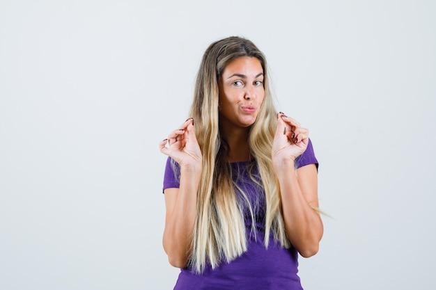 Blonde dame in violet t-shirt geld gebaar tonen en sluw, vooraanzicht op zoek.