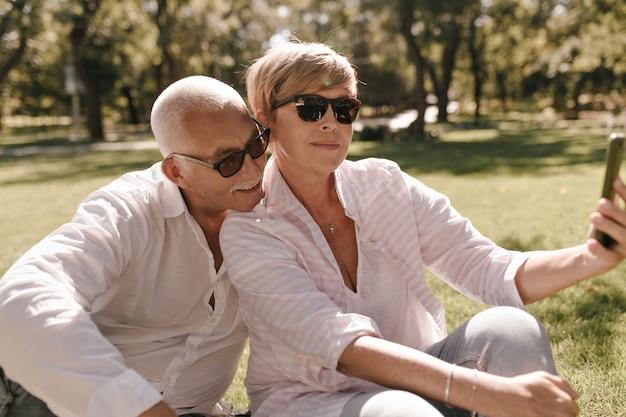 Blonde dame in zonnebril, gestreepte stijlvolle blouse en spijkerbroek. zittend op het gras en het maken van selfie met besnorde man in wit overhemd buiten.