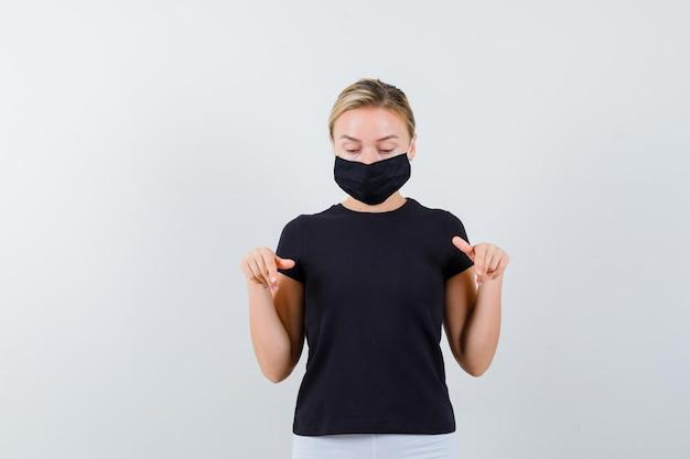 Blonde dame in zwart t-shirt, zwart masker dat naar beneden wijst en er voorzichtig geïsoleerd uitziet