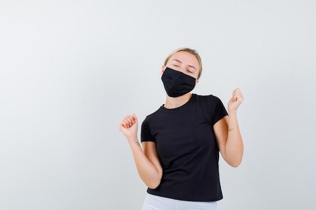 Blonde dame in zwart t-shirt, zwart masker dat winnaargebaar toont en er gelukkig uitziet