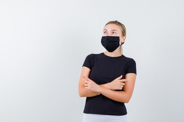 Blonde dame in zwart t-shirt, zwart masker wijzend naar beide kanten en zelfverzekerd geïsoleerd