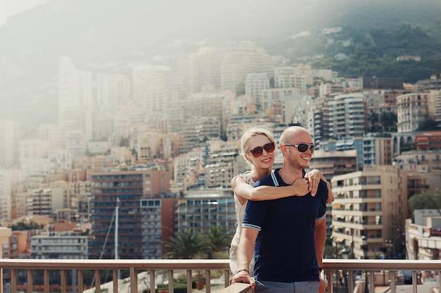 Blonde dame knuffelt kaalkop man met grote cityscape achter de