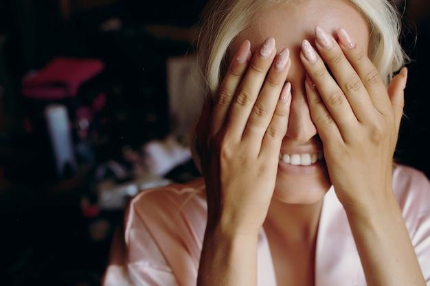 Blonde dame lacht terwijl ze haar gezicht achter de handpalmen verbergt