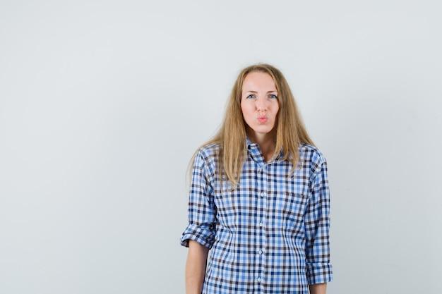 Blonde dame lippen in shirt pruilen en er aantrekkelijk uitzien,