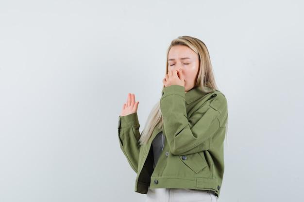 Blonde dame neus knijpen vanwege slechte geur in jas, broek en walgt, vooraanzicht.
