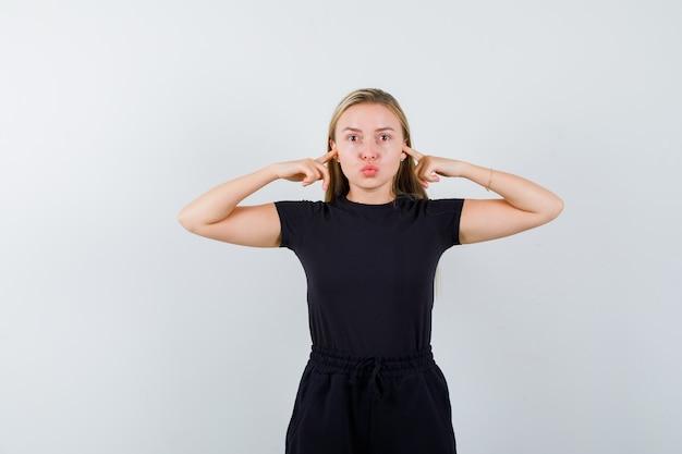 Blonde dame oren met vingers inpluggen, lippen pruilen in zwarte jurk en voorzichtig kijken. vooraanzicht.