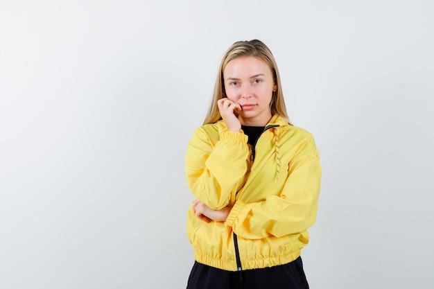 Blonde dame permanent in denken pose in trainingspak en op zoek verstandig, vooraanzicht.