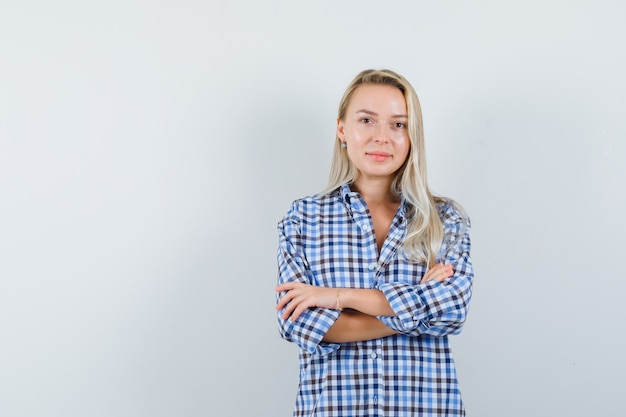 Blonde dame permanent met gekruiste armen in geruit overhemd en op zoek zelfverzekerd