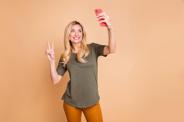Blonde dame poseren tegen de beige muur