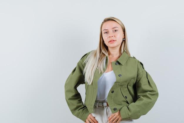 Blonde dame poseren terwijl staande in jas, broek en op zoek schattig, vooraanzicht.