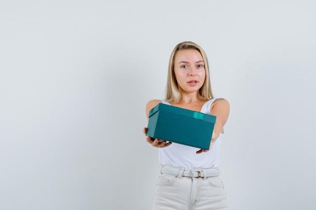 Blonde dame presenteert huidige doos in hemd, broek en ziet er schattig uit. vooraanzicht.