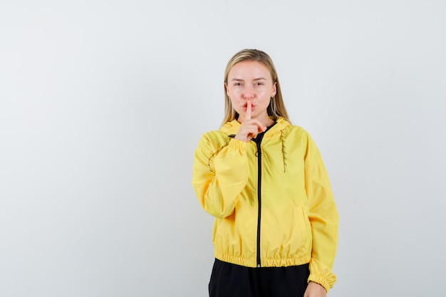Blonde dame stilte gebaar in trainingspak tonen en op zoek verstandig, vooraanzicht.
