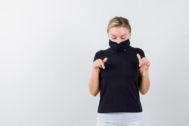 Blonde dame wijst naar beneden in zwart t-shirt, zwart masker en kijkt voorzichtig geïsoleerd