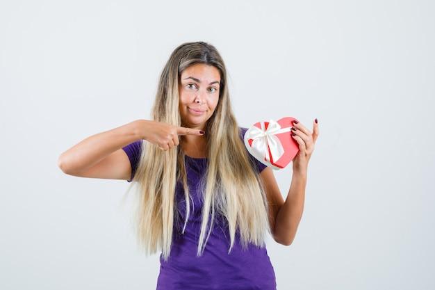 Blonde dame wijzend op geschenkdoos in violet t-shirt en kijkt blij, vooraanzicht.