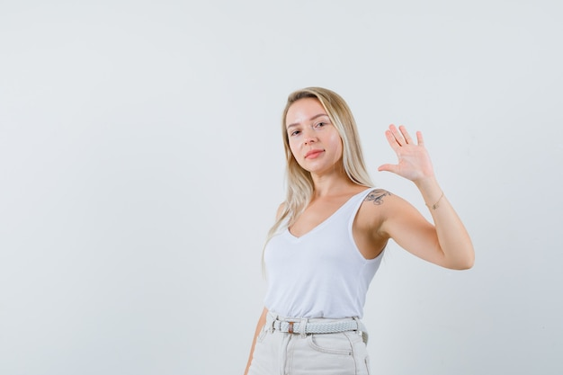 Blonde dame zwaait met de hand om afscheid te nemen in hemd, broek en ziet er zelfverzekerd uit