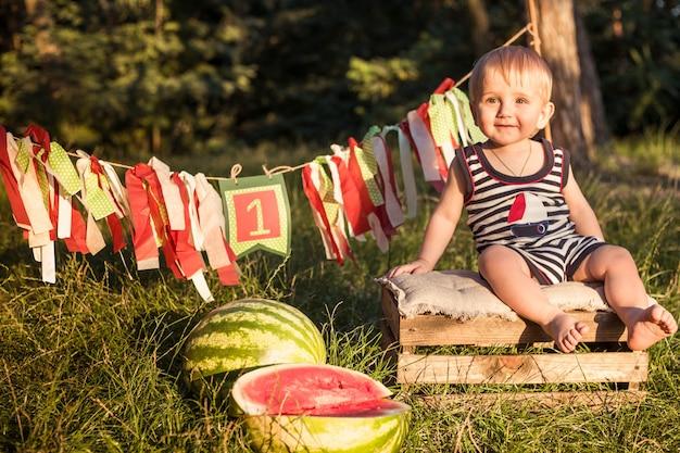 Blonde de jongen zit omringd door watermeloenen op een de zomerdag