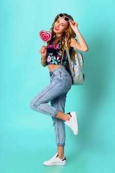Blonde de mannequinmeisje die van de schoonheid kleurrijke roze doughnut houden. grappige vrolijke vrouw met snoep, dessert. dieet, dieet concept. junk food. felle kleuren.