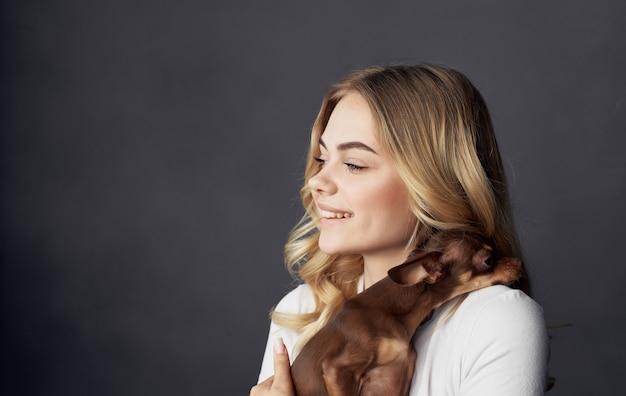 Blonde die een klein de vriendschapsclose-up van het hondhuisdier houdt. hoge kwaliteit foto