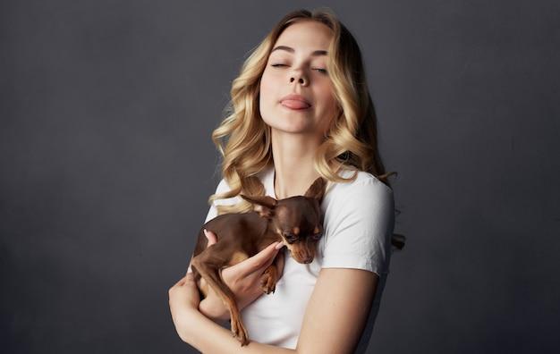 Blonde die een klein de vriendschapsclose-up van het hondhuisdier houdt
