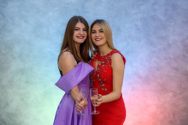 Blonde en brunette vrouw in elegante avondjurken poseren met champagneglazen