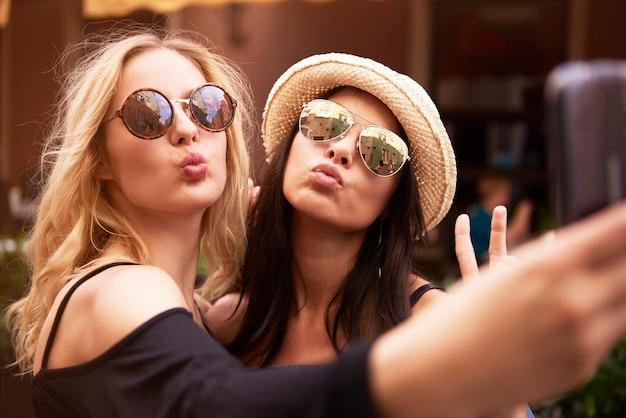 Blonde en donkere haarmeisjes die een selfie nemen