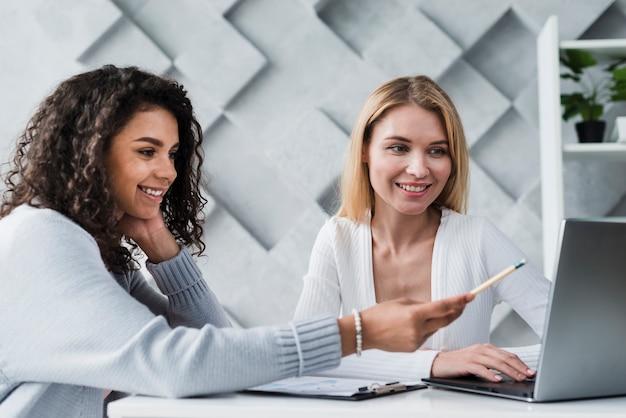 Blonde en etnische collega's die met laptop werken