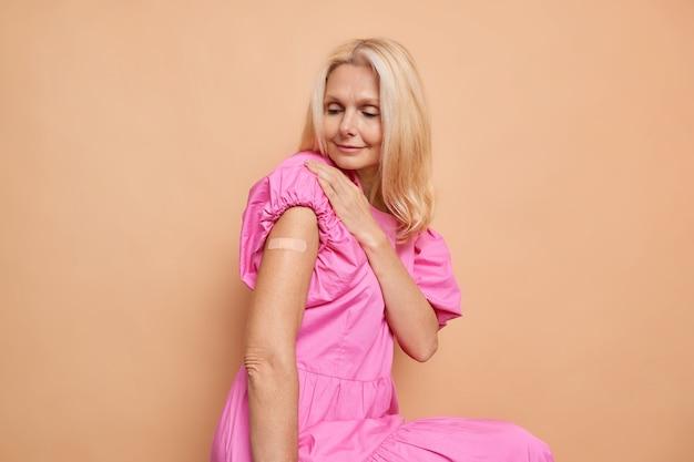 Blonde europese vrouw van middelbare leeftijd kijkt naar haar gevaccineerde arm krijgt vaccininjectie en draagt roze jurk geïsoleerd over beige muur
