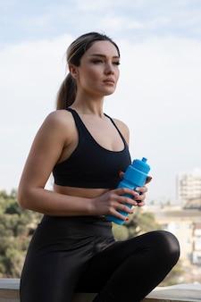 Blonde fitte vrouw in zwarte top die buiten staat met een fles water.