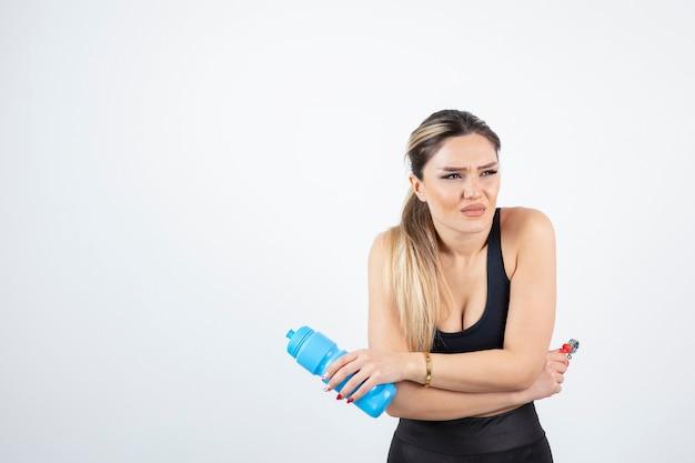 Blonde fitte vrouw in zwarte top die een fles water met expander vasthoudt.