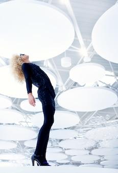 Blonde futuristische vintage sexy vrouw in zwart op moderne indoor volledige lengte