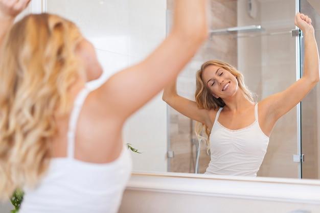Blonde gelukkige vrouw die zich uitstrekt in de ochtend