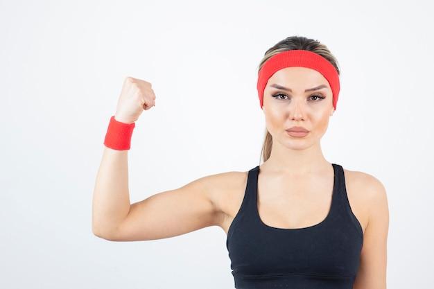 Blonde geschikte vrouw in zwarte sportkleding die staat en biceps toont.