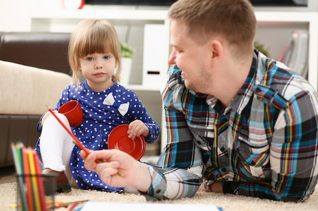 Blonde glimlachende meisjegreep in wapenpotlood tekening iets samen met papa. mooie vrouwelijke jonge kunstenaar minderjarige baby-sitter kunst vreugde jeugd ontwikkeling ouder levensstijl jeugd schilder
