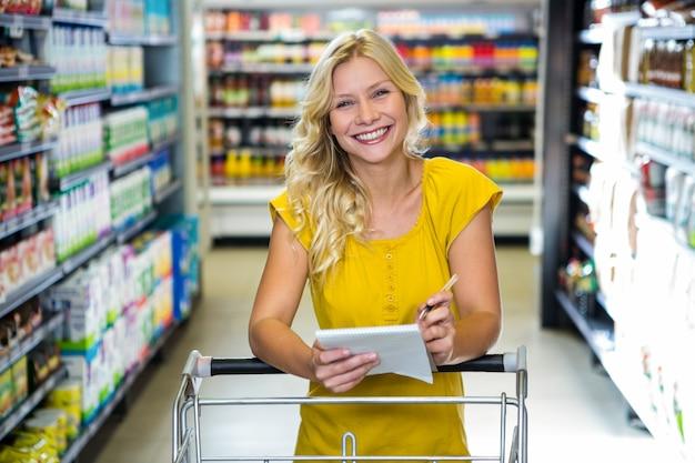 Blonde glimlachende vrouw die lijst controleert