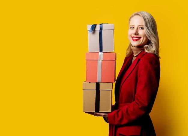 Blonde glimlachende vrouw in rode jas met giftdozen op gele muur