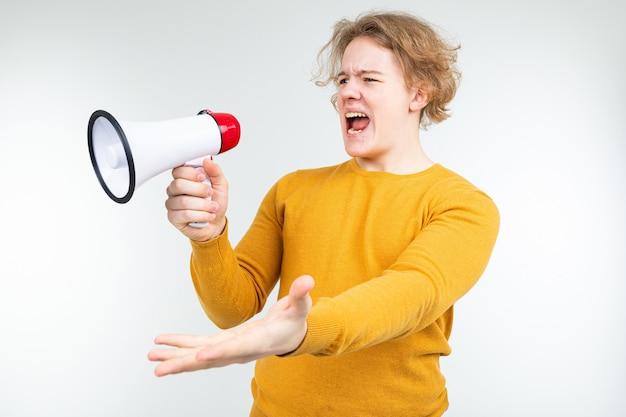 Blonde golvende kerel die nieuws schreeuwt in een luidspreker op een witte studioachtergrond