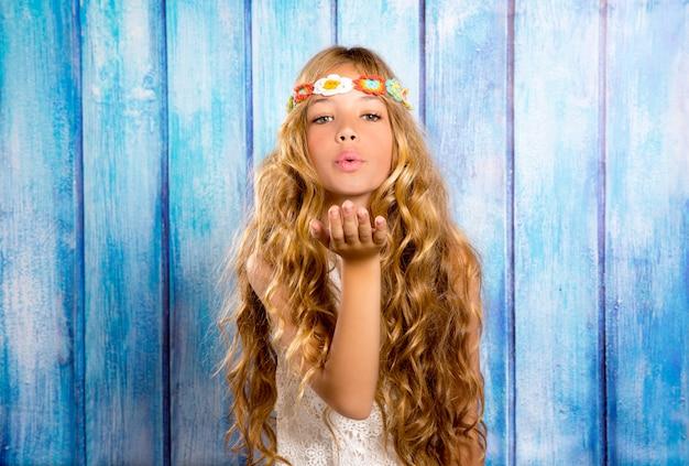 Blonde het meisjes blazende mond van hippiekinderen met hand