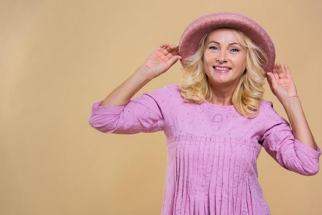 Blonde hogere vrouw die een roze hoed draagt